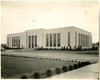 Large government office building with tall windows, manicured lawn