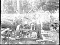 Two men standing beside gasoline-powered log saw.