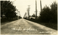 View down center of long stretch of road lined on both sides with power line poles