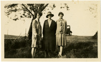 Three women pose in field with tree and car behind them