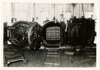 Worker stands next to open door of center retort machine, with pallet