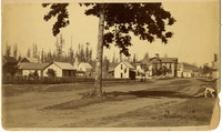 Main street of early frontier Lynden, WA, with church and steeple in middle background