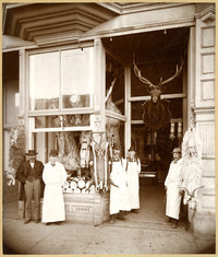 Four men in butcher's aprons and a man in a suit stand outside butcher shop with several animal carcasses hanging in windows
