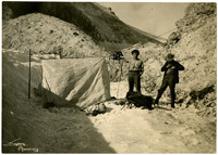Two men are posed with a tent on a patch of snow.