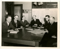 Six men, including Charles F. Larrabee, seated around a table