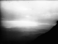 View across unidentified mountain ranges towards a sunset or sunrise.