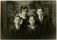 Formal studio portrait of four young people, two boys and two girls