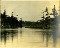 Water scene of very narrow passage through rocky, forested coastlines with modest wooden dock on righ