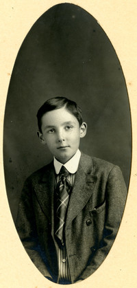 Oval studio portrait photograph of boy in suit