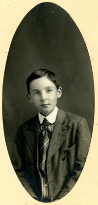 Oval studio portrait photograph of boy in suit