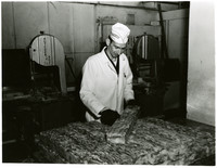 A man in a lab coat inspects slabs of frozen crab meat in a cannery