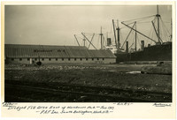 Large steamship moored next to Pacific American Fisheries' Bellingham warehouse with Great Northern Railway tracks in foreground