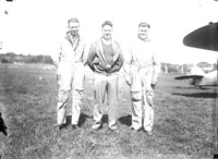 Three men standing in grassy airfield posing for photograph