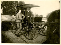 Man stands next to two people seated in horse-drawn buggy