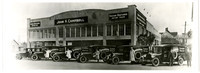 Exterior of two-story brick John F. Campbell auto dealership with six early model Barker's Bakery trucks and their drivers parked in front