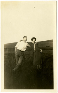 Man and woman stand arm-in-arm in pasture
