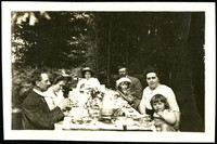 Nine adults and children sit at a well-appointed table outdoors in the woods
