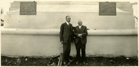 Two unidentified men standing in front of the Peace Arch