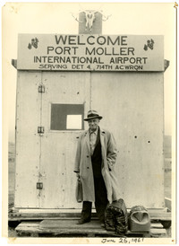 "Man in over coat stands with luggage outside small hut with sign that reads ""Welcome Port moller International Airport"""