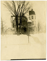 Snowy scene of front exterior of large three-story residence with turrett
