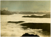 Mountaintop view of low clouds covering valleys in foreground with sharp peaks spanning the horizon