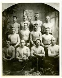 Twelve men in athletic shirts pose in three rows in studio portrait