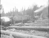 Three men beside large log chained onto rail-car