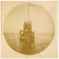 Circular photograph of several men and women crowd the deck and pilot house roof of small ferry