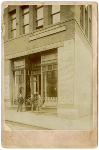 Three men stand outside Fairhaven Pharmacy, with advertisements painted on sides of building, 12th Street, Bellingham, WA