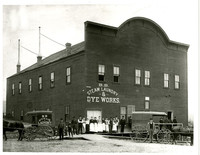 Women in long work aprons and several men stand outside large building of B.B. Steam Laundry & Dye Works with two horse-drawn delivery carriages in front