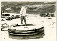Unidentified woman standing in snow looking down at a large round wooden object filled with snow