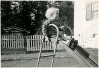 Child seated on top of slide