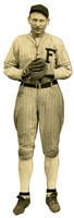 """Man poses in baseball uniform with glove and """"F"""" on his uniform."""