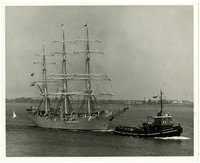 Norweigan full rigged ship called the Christian Radich  towed by a tugboat named Helen M. Mcallister and followed by a sailboat.