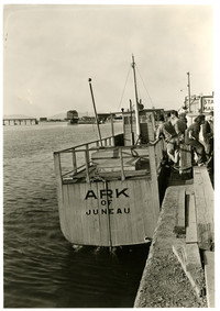 """Stern of a wooden tub-like boat called the """"Ark of Juneau"""" at dock"""