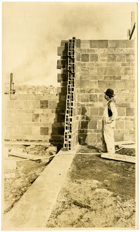 """A mason stands looking at a partially-built brick wall of Pacific American Fisheries' """"hollow tile"""" warehouse"""