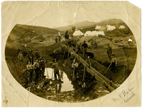 Sixteen men, two horses, and a dog standing in and above a wet, muddy pit with a long, elevated sluceway
