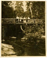 Several people pose on wooden bridge over Whatcom Creek