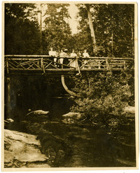 Several people pose on wooden bridge over Whatcom Creek