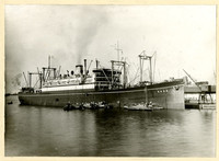 Steamship President McKinley at dock with several smaller crafts laden with cargo pulled alongside