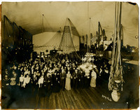Large group of finely dressed men and women in a ball room gather at center of room to pose for photograph