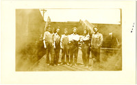 Six men in overalls and work clothes pose on a wooden deck