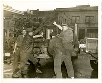 Four unidentified men lifting a heavy object into the back of a pick up truck.