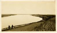 Two men standing on bank of Bear River, Alaska