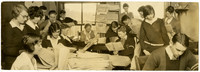 Fairhaven High School school students work among desks piled high with papers, possibly a school newspaper classroom
