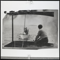 Man seated in the stern of a boat that is towing a sailboat with two women on board.
