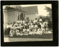 Unidentified group gathered next to house