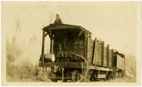 A man sits on roof of railroad car, above a pump mounted to back platform