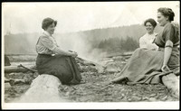 Three women sit in conversation on logs at a beach