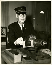 Andrew Loft, railway conductor, in his uniform, sitting at desk with slide projector